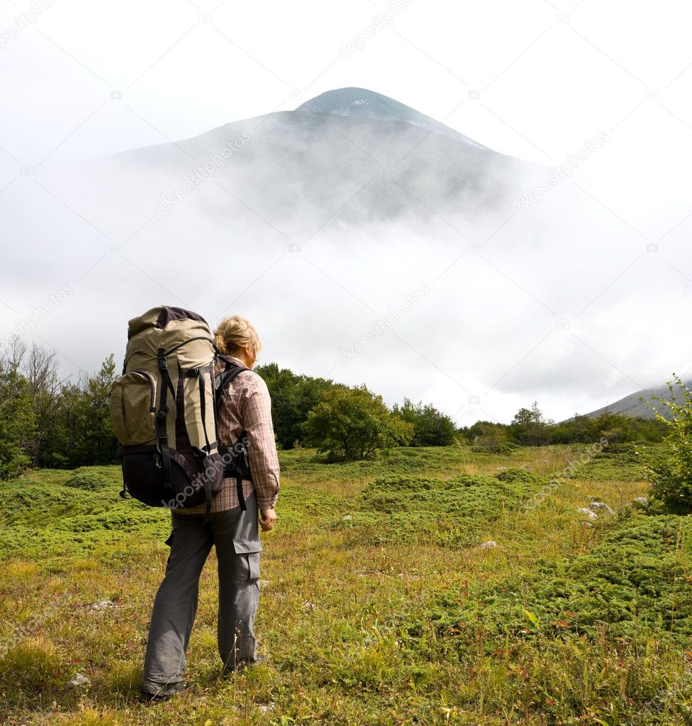 Hiker in mountains on green glade — Photo #6974982