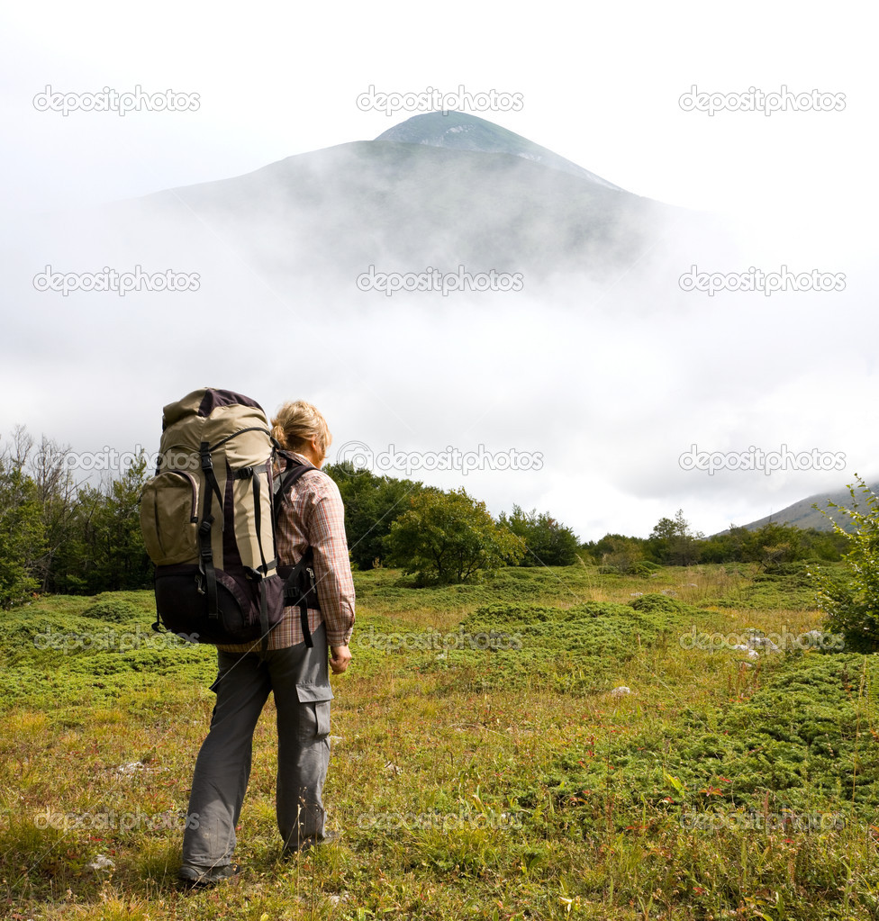 Hiker in mountains on green glade — Foto Stock #6974982