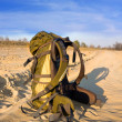 Backpack on sandy road — Stock Photo