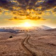 Mountain road on sunset background — Stock Photo