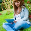 Stock Photo: Young woman reading in tablet pc