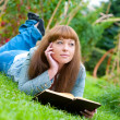 Young woman reading a book lying on the grass — Stock Photo #6764332