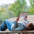 Stock Photo: Young woman reading a book lying on the bench