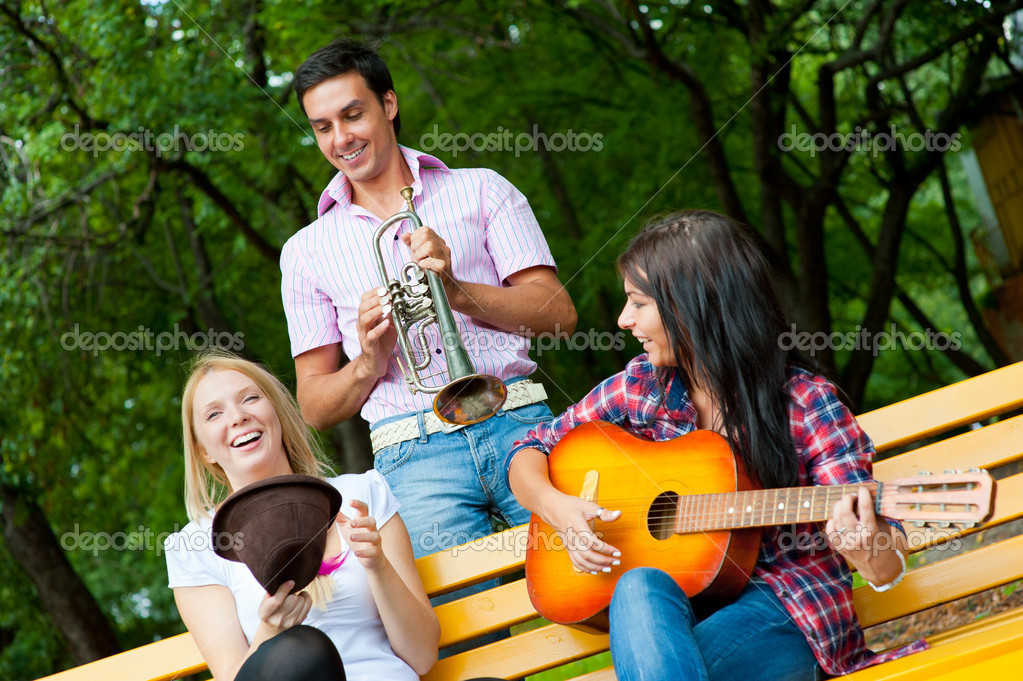 Young friends play the guitar and trumpet in the park — Stock Photo #6813166
