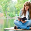 Young woman reading a book sitting on the bench — Stock Photo #6863768