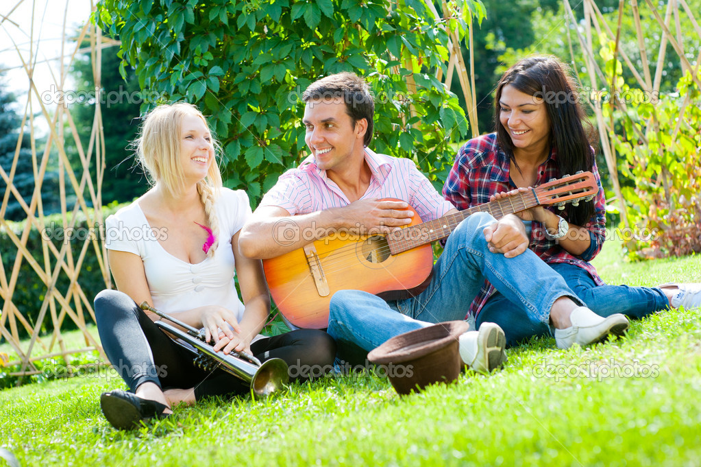 Young friends play the guitar and having fun in the park  Stock Photo #6863749