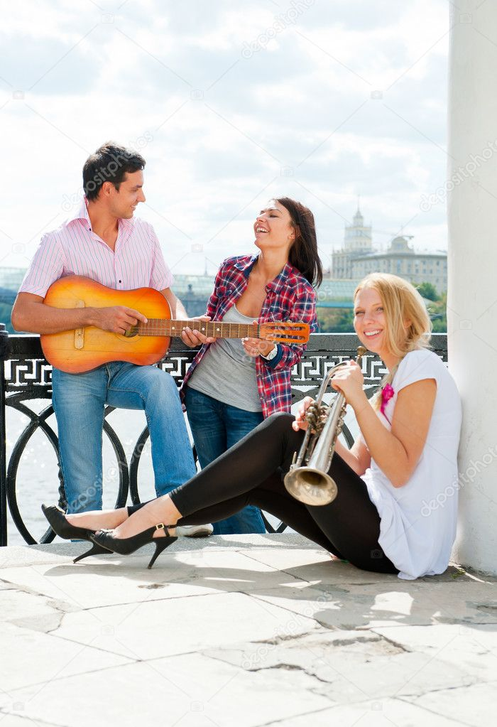 Young friends play the guitar and trumpet on the embankment — Stock Photo #6863755