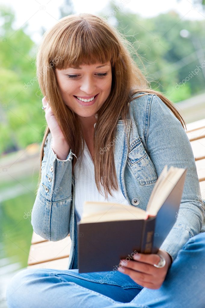 Young woman reading a book sitting on the bench in the park — Stock Photo #6863785