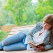 Young woman reading a book sitting on the bench — Stock Photo #6928134