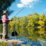 Senior fisherman catches a fish — Stock Photo #6957550