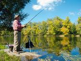 Senior fisherman catches a fish — Stock Photo