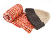 Tortile multicolor wool scarf and cap over white background — Stock Photo