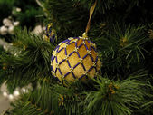 Yellow ball on the christmas fir — Stock Photo