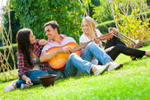 Young friends play the guitar and trumpet — Stok fotoğraf