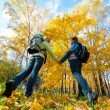 Happy young couple with backpacks in the park — Stock Photo