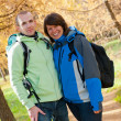 Happy young couple with backpacks in the park - Stock Photo