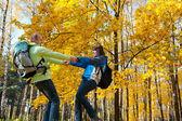 Glada unga par med ryggsäckar i parken — Stockfoto