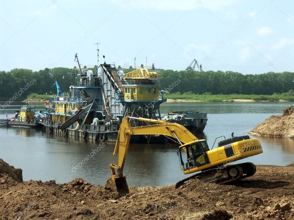 The excavator works in the sand-pit on the river bank. There are some working ships in the background. — Stock Photo #7609447