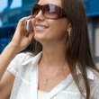 Cute smiling girl speaks on a mobile phone — Stockfoto