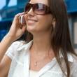 linda chica sonriente habla por un teléfono móvil — Foto de Stock