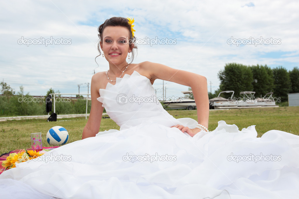 Young beautiful bride sitting on the grass — Stock fotografie #6813197