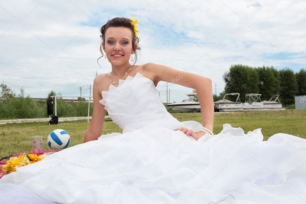 Young beautiful bride sitting on the grass — Foto de Stock   #6813197