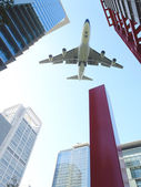 Airplane and buildings — Stock Photo