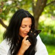 Dark haired woman with a cat outdoor — Stock Photo #7075627