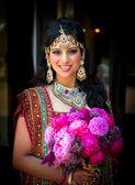 Lächelnd indische braut mit blumenstrauß — Stockfoto
