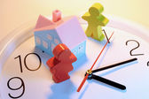 Wooden Figures and Toy House on Clock — Stock Photo