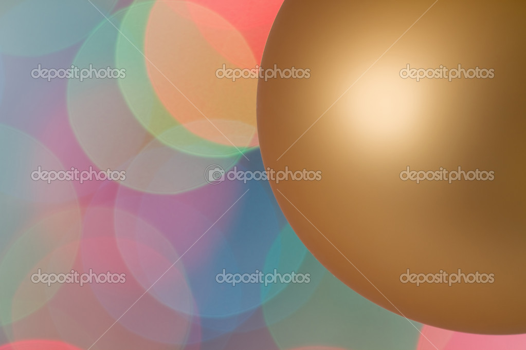 Gold Christmas bauble against Christmas tree lights. — Stock Photo #7866091