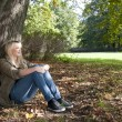 Stock Photo: Young womsitting in park