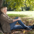 Young woman sitting in the park — Stock Photo