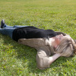 Young woman lying on a meadow - Stock Photo