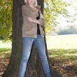 Young woman stands on a tree — Stock Photo