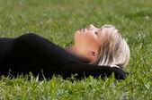 Joven mujer acostada en un prado — Foto de Stock