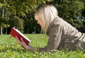 Young woman reading a book on a meadow — Stock Photo