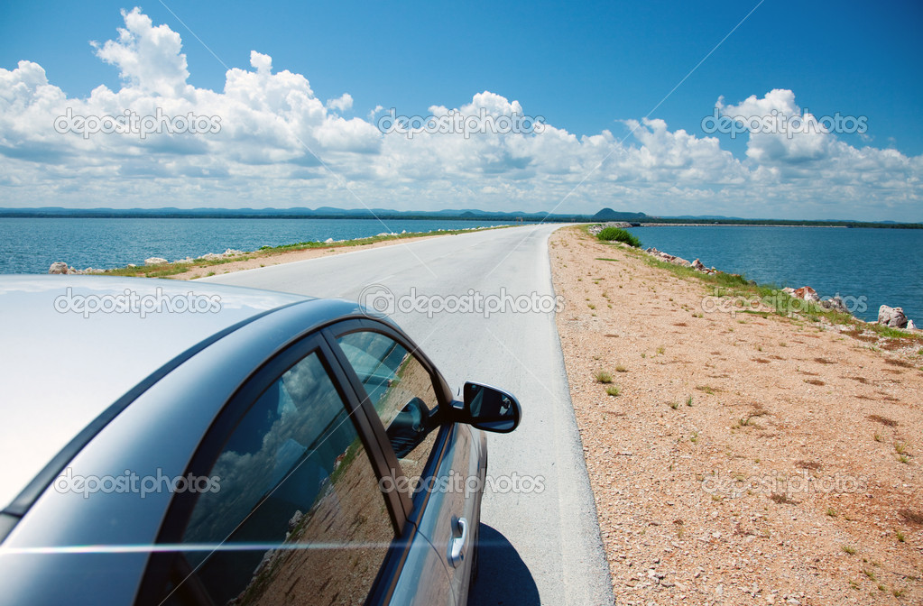 Car driving across ocean by the road — Stock Photo #7142661