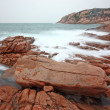 Rocky sea coast and blurred water — Stock Photo