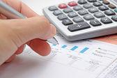 商人的手显示图上用笔的财务报告. — 图库照片