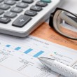 Stock Photo: Stock chart with calculator,pen and eyeglasses