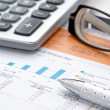 Stock chart with calculator,pen and eyeglasses — Stock Photo