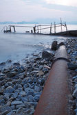 Old metal pipe and road to sea — Stock Photo