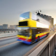 Speed bus through sunset road — Stock Photo