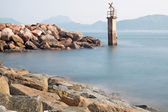 Lighthouse on a Rocky Breakwall: A small lighthouse warns of a r — Stock Photo