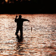 Stock Photo: Silhouette of fishermpulling fish