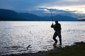 Silhouette of a fisherman pulling a fish — Stock Photo