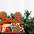 Постер, плакат: Two gingerbread men in cart among Christmas greens with copy space
