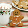 Happy gingerbread man cookie by cup of cocoa — Stock Photo