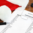 Santa's Naughty and Nice gift list with glasses and hat. — Stock Photo #7565196